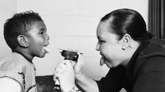 Doctor checking the mouth of a child using medical tool