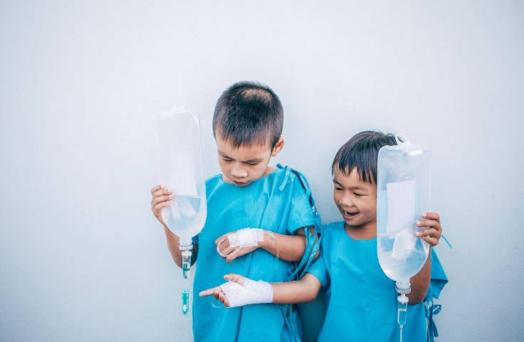 Two young boys wearing blue hospital gowns playing outside